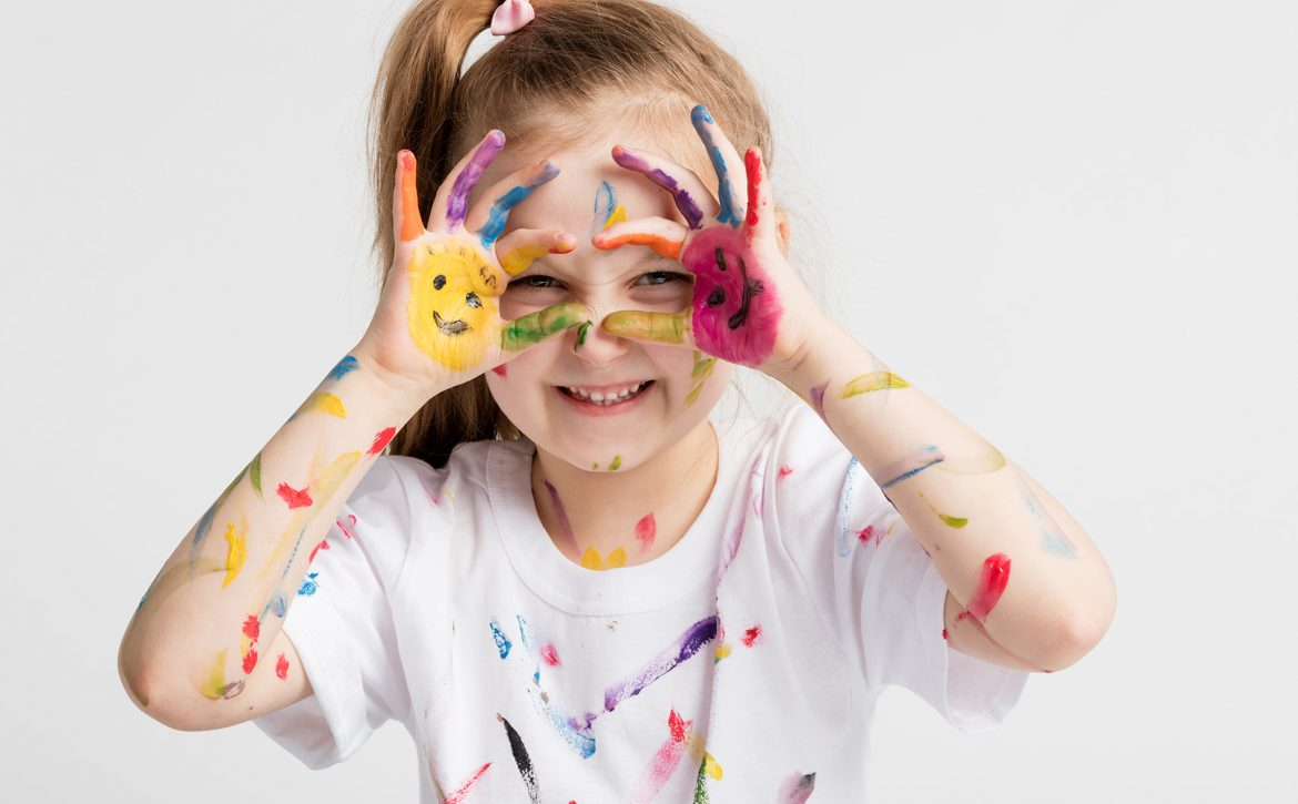 Little girl covered in paint making funny faces.